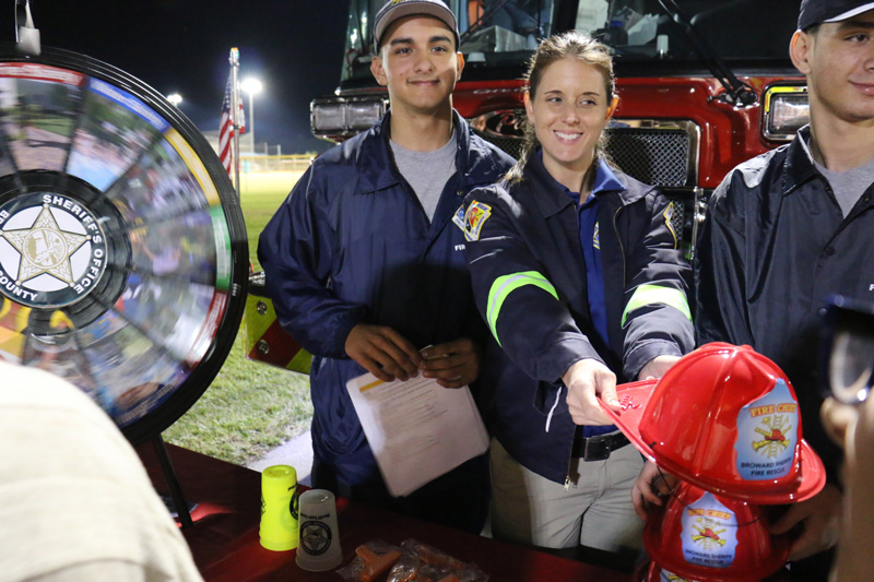 Fire personnel and firewoman handing toy hat