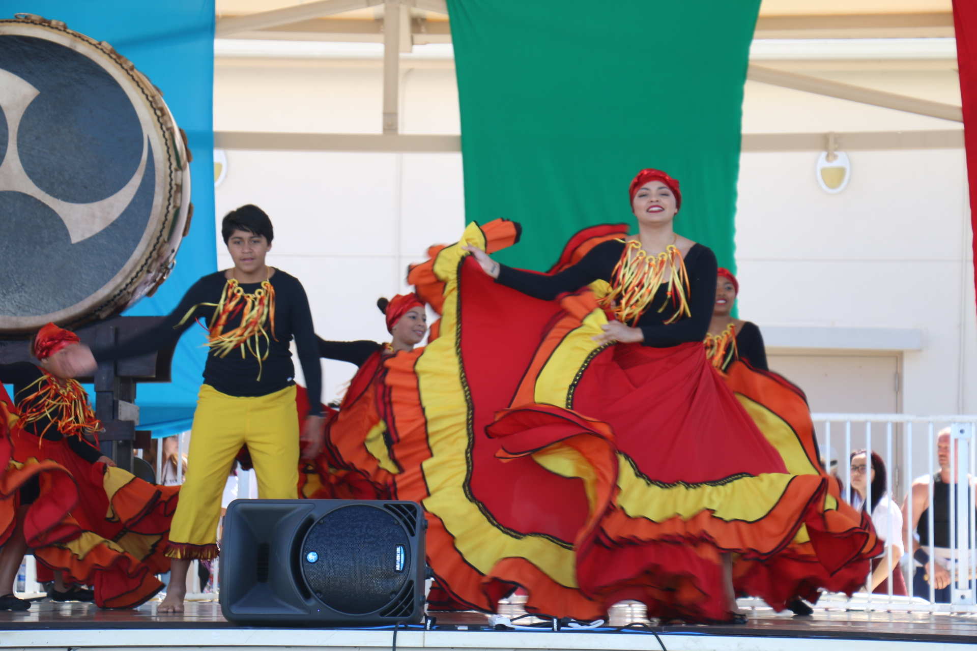 male and female dancers on stage in red, yellow and black costumes
