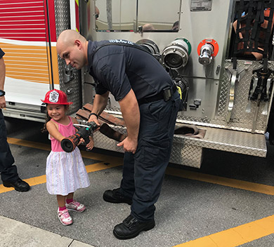 Little girl with firefighter in front of fire truck