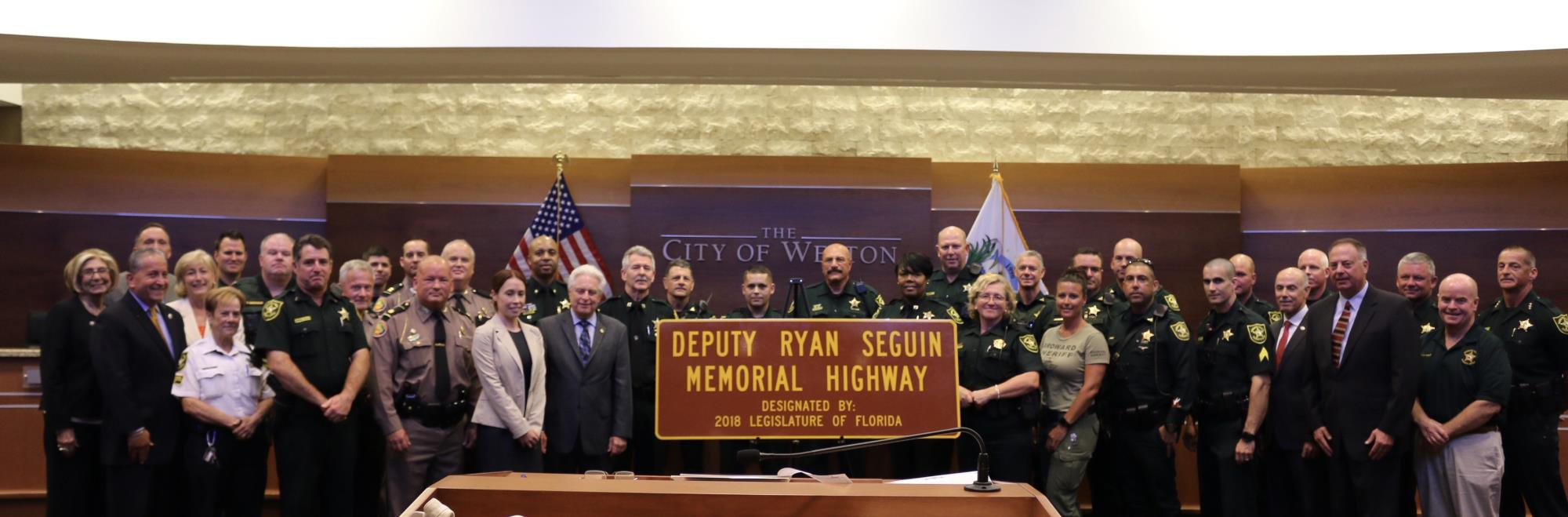 Large group of people in front of highway sign honoring Deputy Ryan Seguin