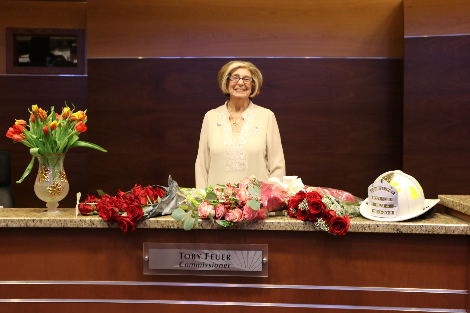 Commissioner Toby Feuer standing in front of her flowers at dais