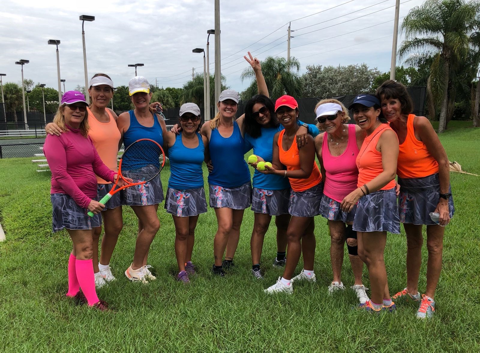 10 women from the Weston Women's Tennis League posing in front of courts