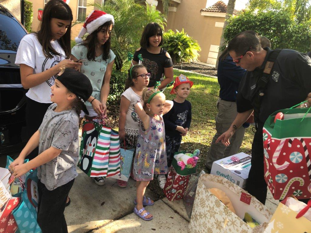 Children getting Christmas gifts from firefighters