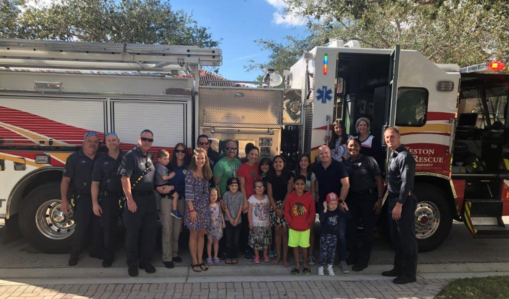 Barnes family and firefighters in front of Weston fire truck