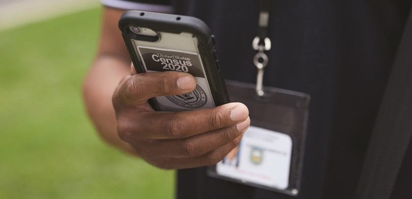 A census worker holding a phone with photo ID