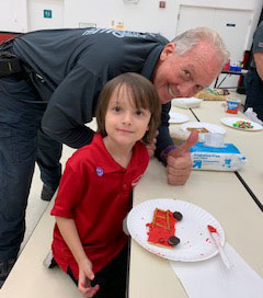firefighter with young school boy at cafeteria table